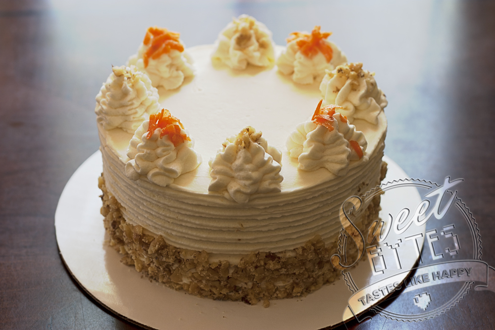 A 3 layer carrot cake with cream cheese frosting, swirls of frosting on top with alternating carrot and walnut sprinkles. How to bake a cake from scratch