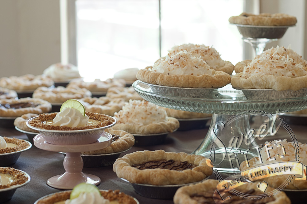 A pie buffet with many different types of mini pies arranged on serving pedastals