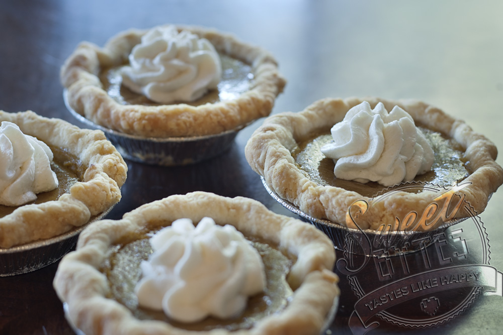 4 mini pumpkin pies with a dollop of whipped cream in the center of each
