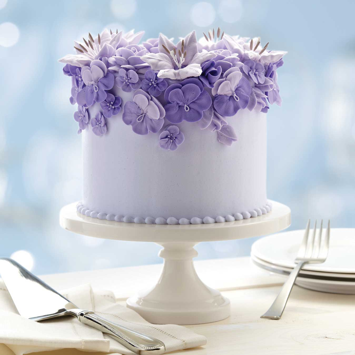 A round layered cake covered in purple buttercream and with piped, royal icing flowers in various shades of violet and lavender on a white cake stand.
