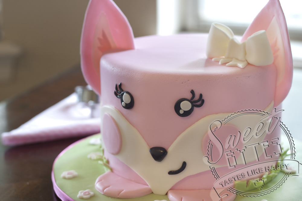 A six inch round cake covered in pink and white fondant to look like a cake shaped girl fox.