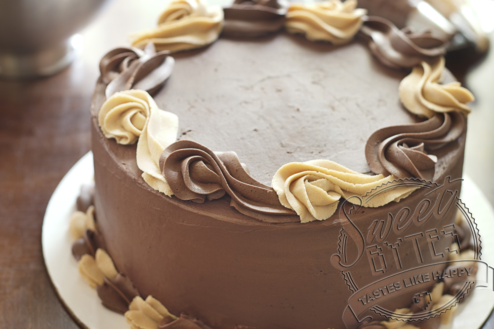 A close up view of the top of a cake. Alternating swirls of peanut butter buttercream frosting and chocolate ganache frosting demonstrate the different types of frosting