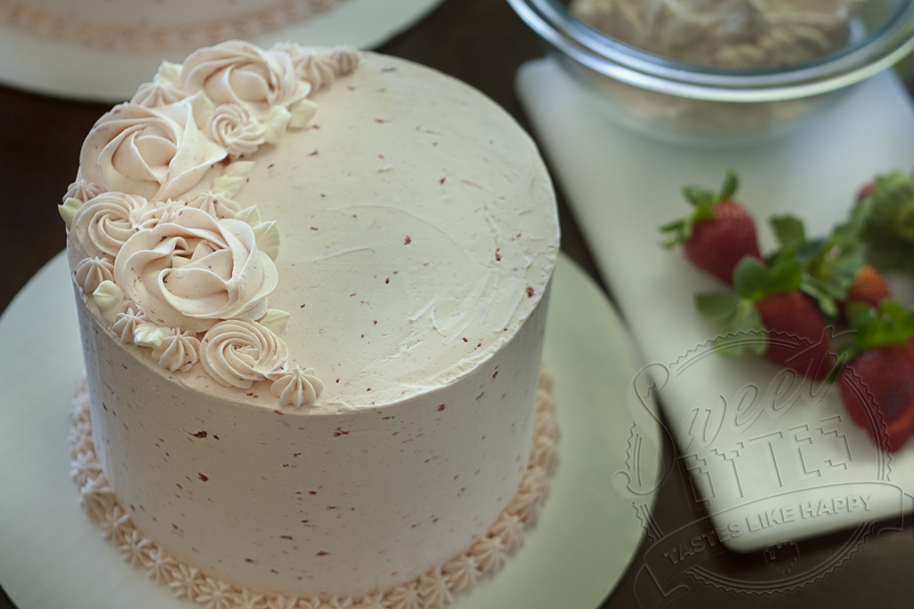 Close up view of strawberry layer cake with strawberry buttercream piped decorations on top