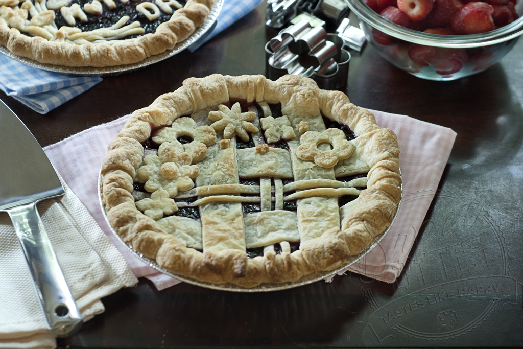 decorated triple berry pie with lattice crust and cut out flowers on top