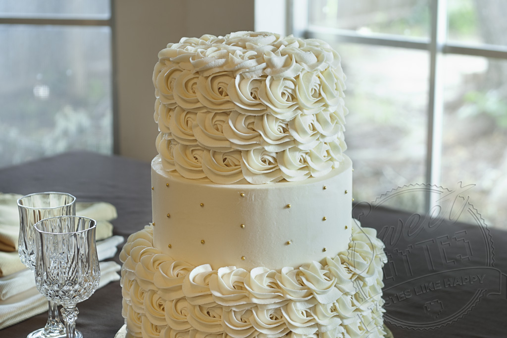 A 3 tiered, cream colored cake with American Buttercream Frosting sitting on a table with two crystal wine glasses