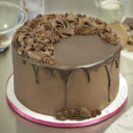 "An 8"" round cake covered with chocolate ganache frosting. Poured chocolate drips down the sides of the cake and piped chocolate ganache decorations cover the top."