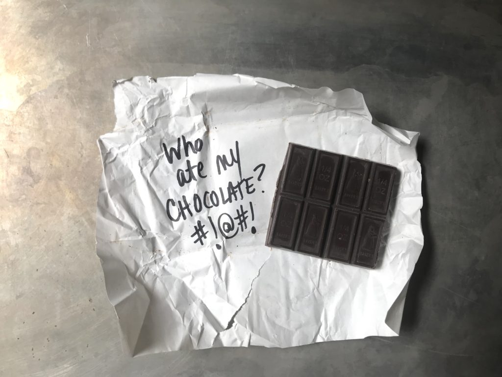 "1/2 a German's Chocolate bar on crumpled open wrapper. ""Who at my Chocolate?"""