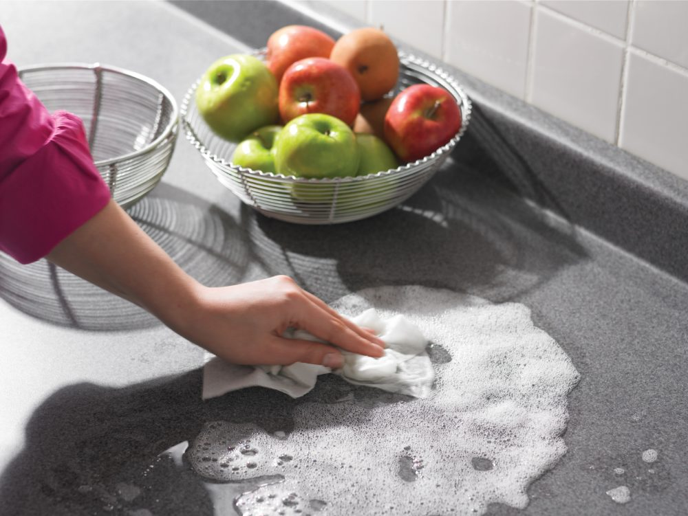 a hand washing a countertop with sudsy water