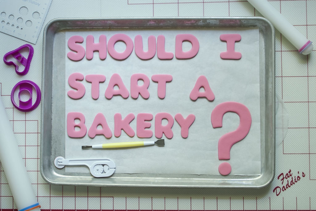 Pink letters cut out of fondant arranged on a half sheet pan covered in parchment paper with a large pink question mark. Two sugar sculpting tools are arranged on the sheet under the phrase Should I Start a Bakery