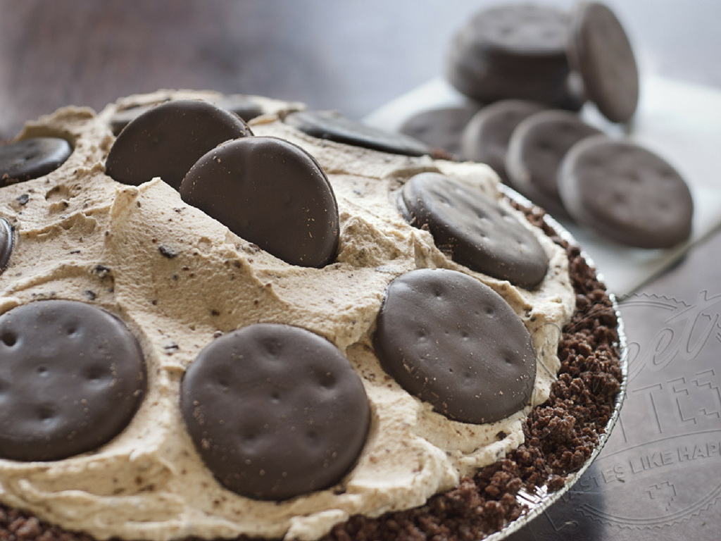 A close up view of a Thin Mint Pie covered in whipped cream with Thin Mints Girl Scout Cookies arranged around the top