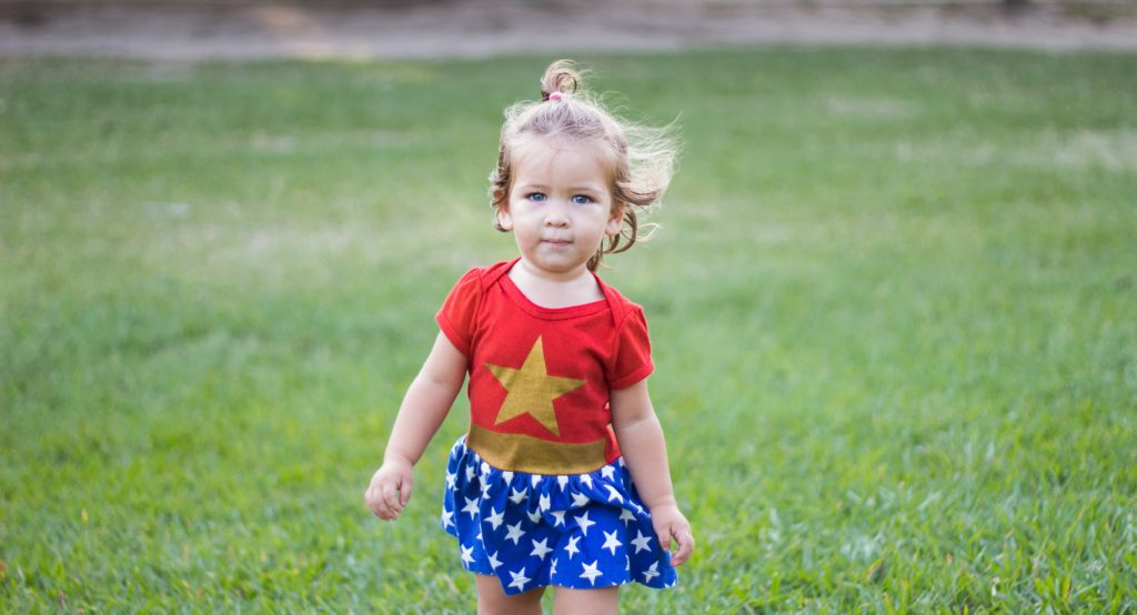 toddler blonde girl in a green field wearing a wonder woman dress