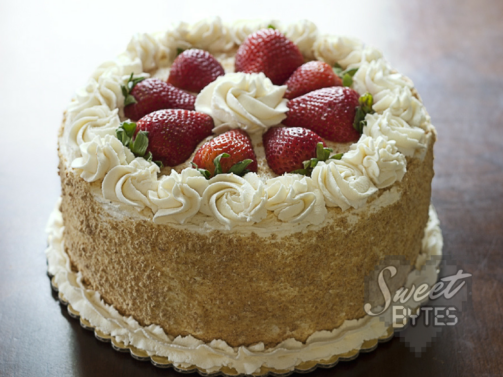 A round layer cake with white whipped cream swirls and halved strawberries on top.