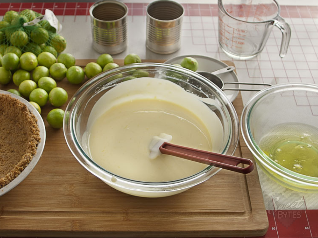 A glass bowl filled with key lime pie filling a red handled spatula sticks out of the bowl.