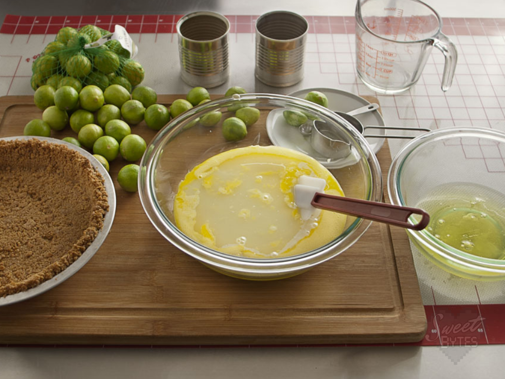 A glass bowl with all of the ingredients for key lime pie being mixed together. A spatula handle is sticking out of the bowl.