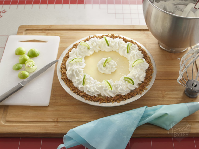 A key lime pie garnished with whipped cream and sliced key limes sitting on a wooden cutting board
