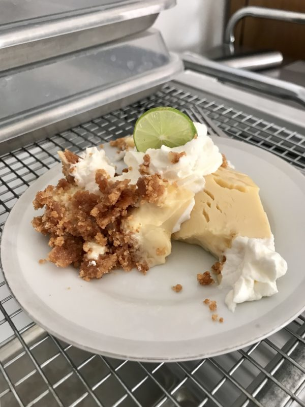 A horribly disfigured piece of key lime pie on a white saucer