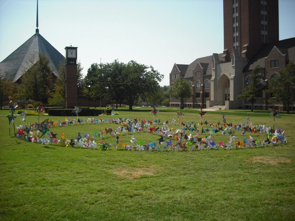 A grassy field at OCU with handmade pinwheels forming a peace sign.