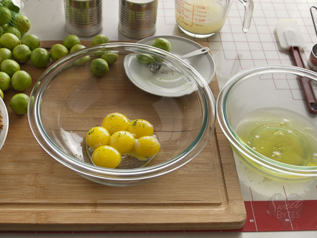 Glass bowl with separated egg yolks and lime zest surrounded by the ingredients for key lime pie on a wooden cutting board