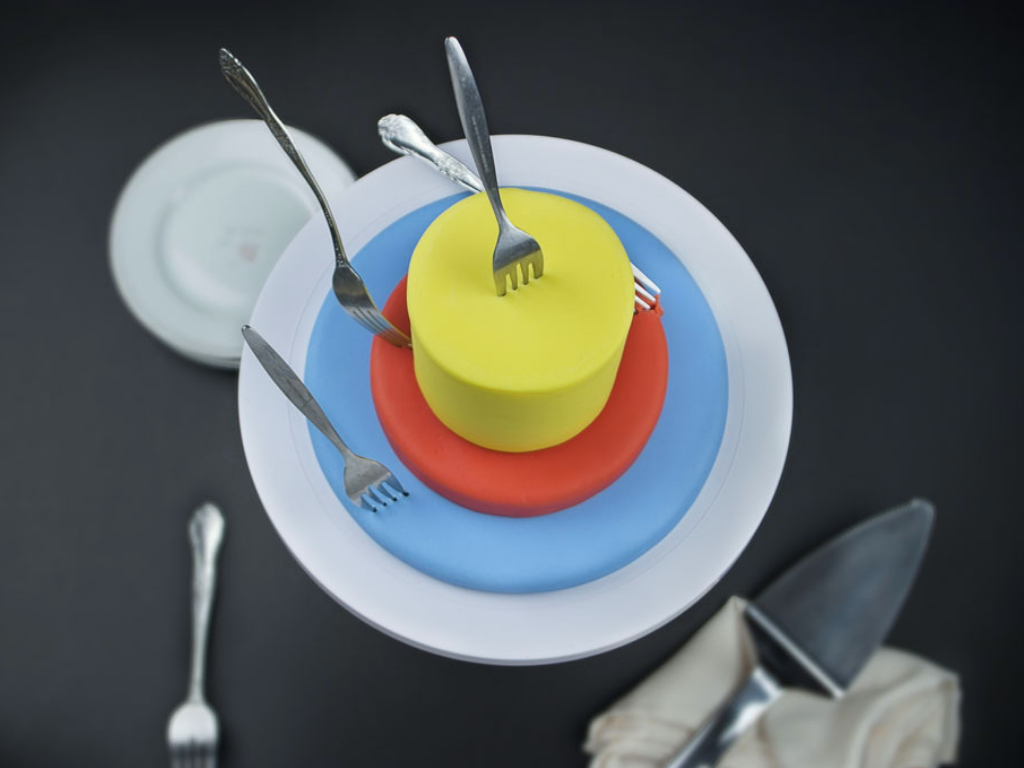 A target like cake with a blue bottom tier, red middle tier, and yellow top tier with forks in it like arrows in a target.