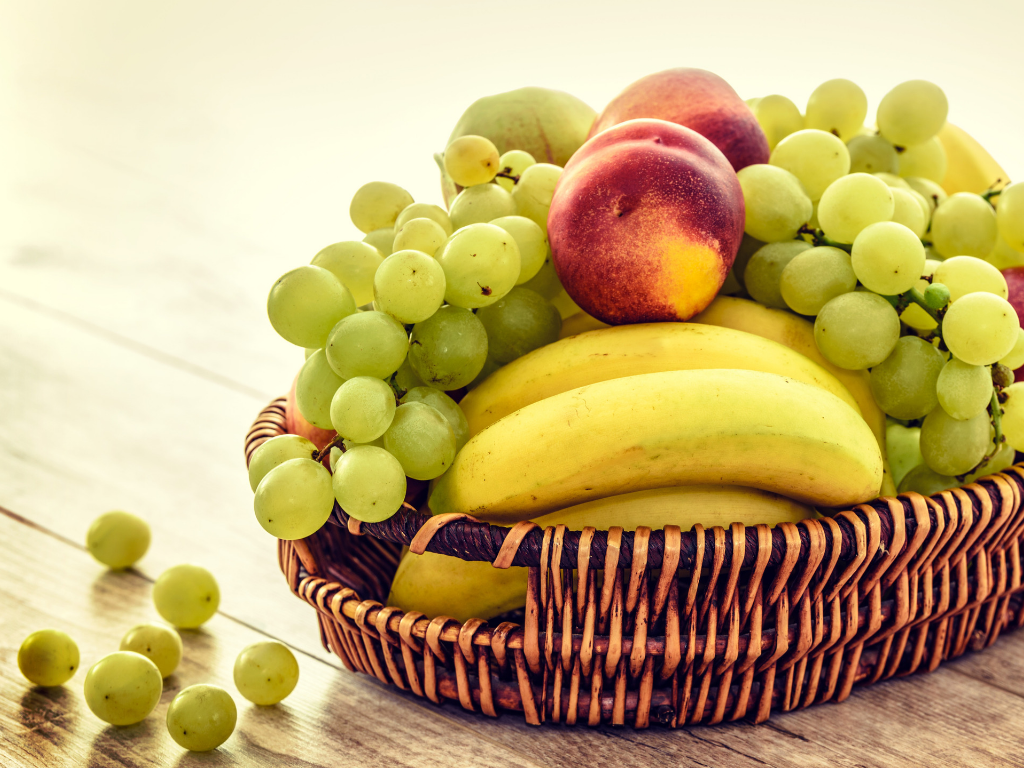 A basket with bananas, peaches, and grapes spilling over the edge on a wooden table