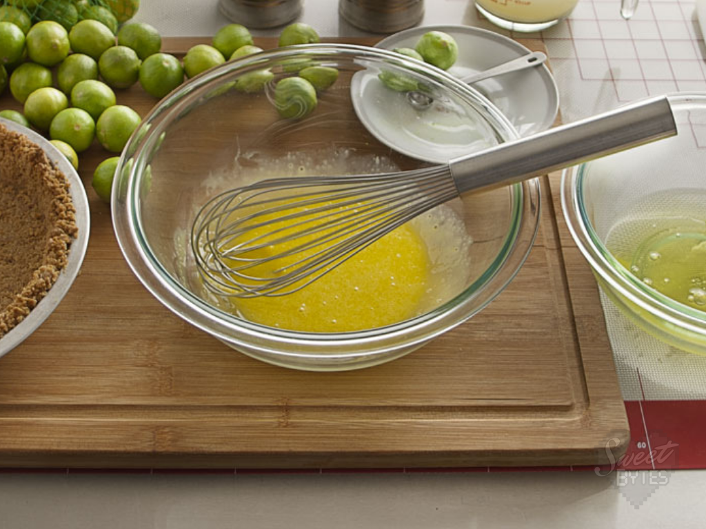 a glass bowl with a stainless steel whisk whisking egg yolks for key lime pie