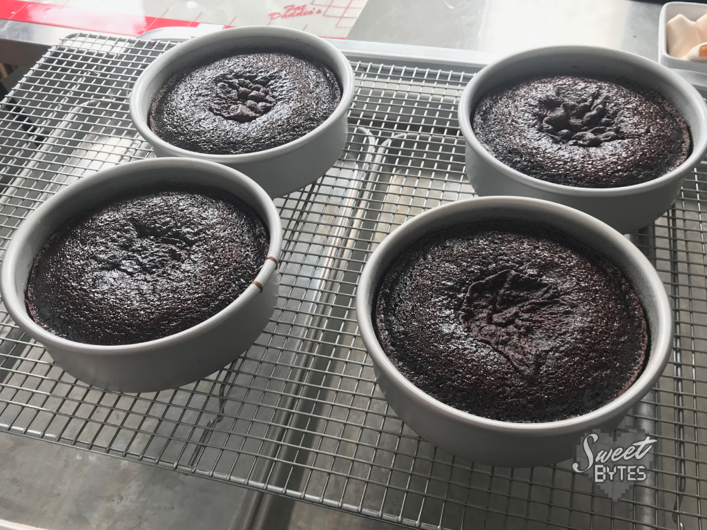 "Four 6"" chocolate cake layers in Fat Daddio's pans cooling on a cooling rack"