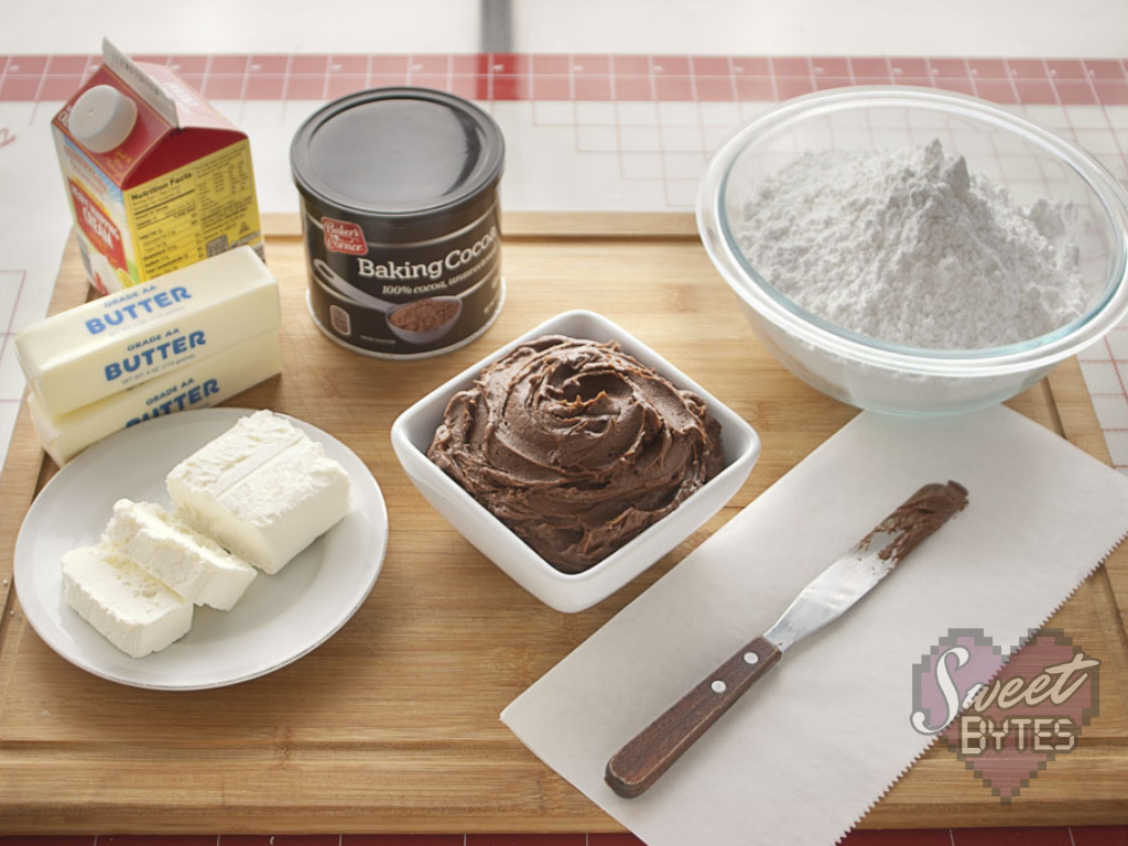A small, white, square bowl of chocolate cake frosting surrounded by the recipe's ingredients
