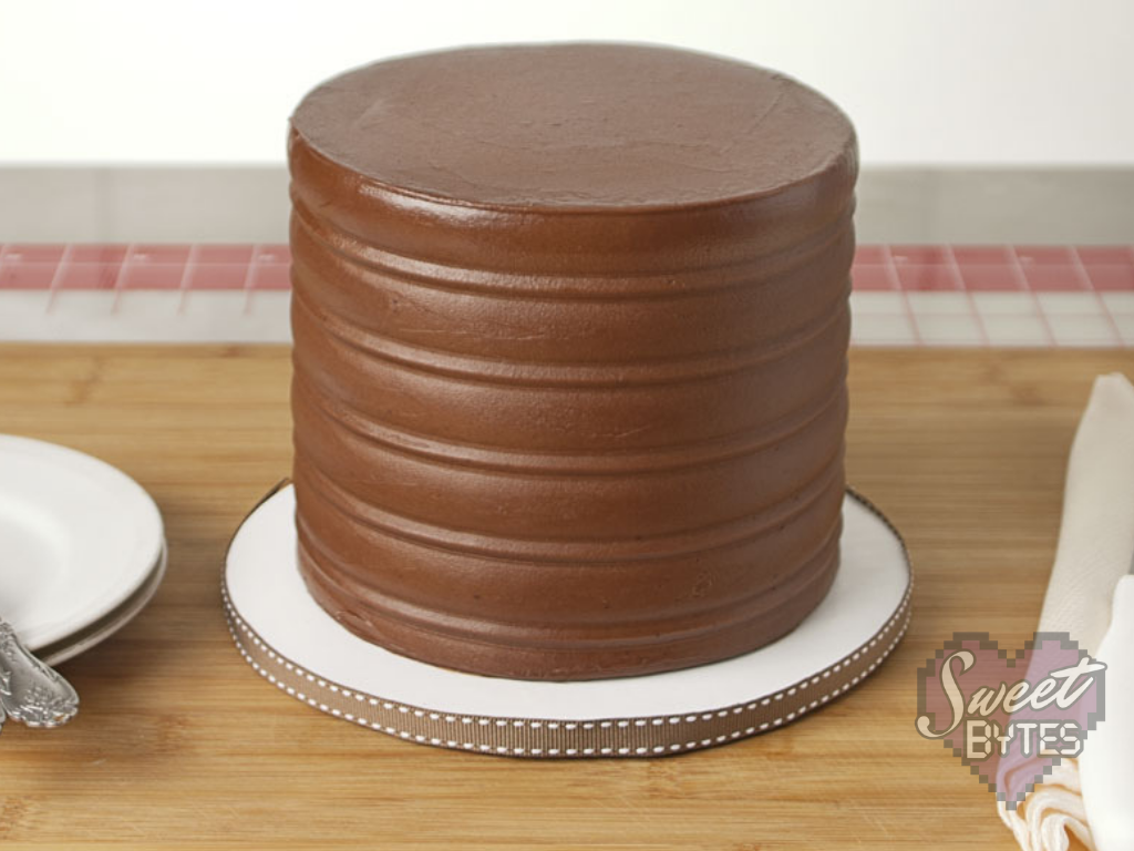 Finished six inch, four layer chocolate cake from scratch frosted with chocolate cake frosting sitting on white cake board with brown ribbon
