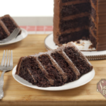 Four layer chocolate cake slice on white dessert plate with the sliced chocolate cake behind it