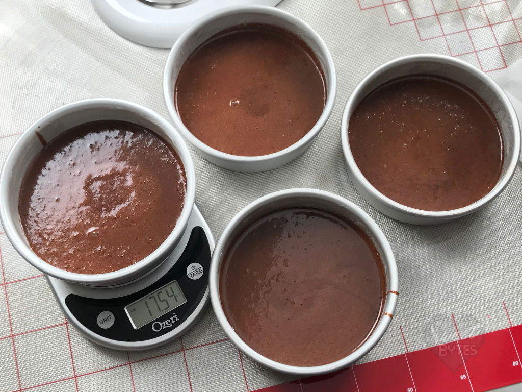 Overhead shot of 4 six inch cake pans filled with chocolate cake batter. The far left pan is sitting on a kitchen scale showing 17.54 ounces