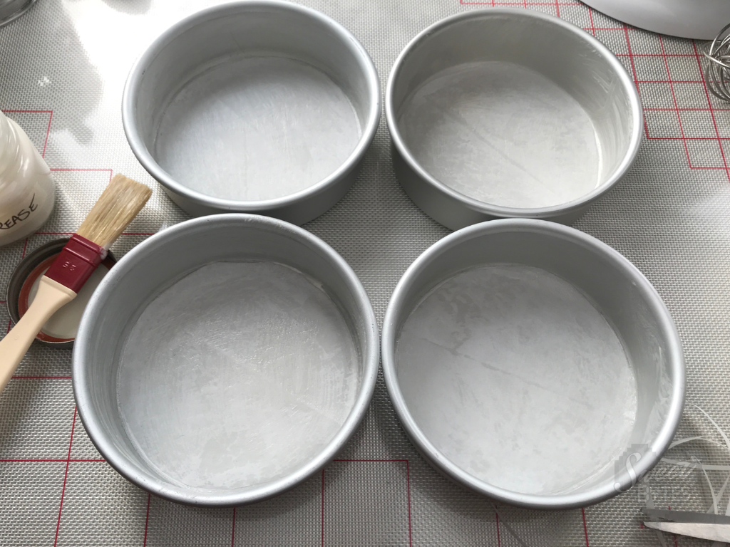 4 six inch, greased cake pans ready to make chocolate cake