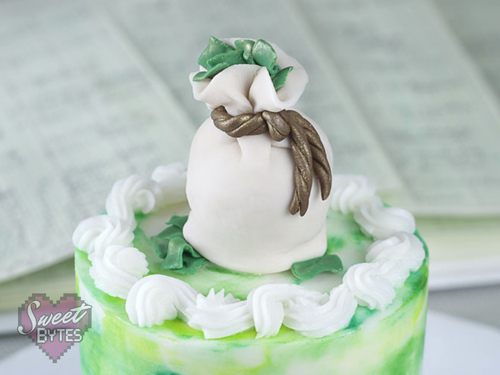 top of a small green and white cake with a fondant money bag cake topper with green fondant money coming out of the top and bottom for the costs of bakery items