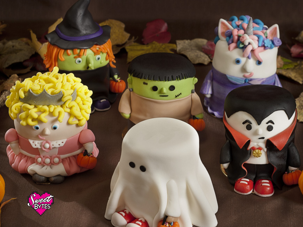 A group shot of 6 mini Halloween cakes covered in fondant. A ghost, princess, Frankenstein, Dracula, witch, and unicorn
