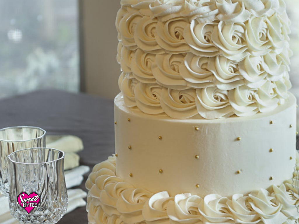 Close up of a 3 tiered cake with vanilla buttercream