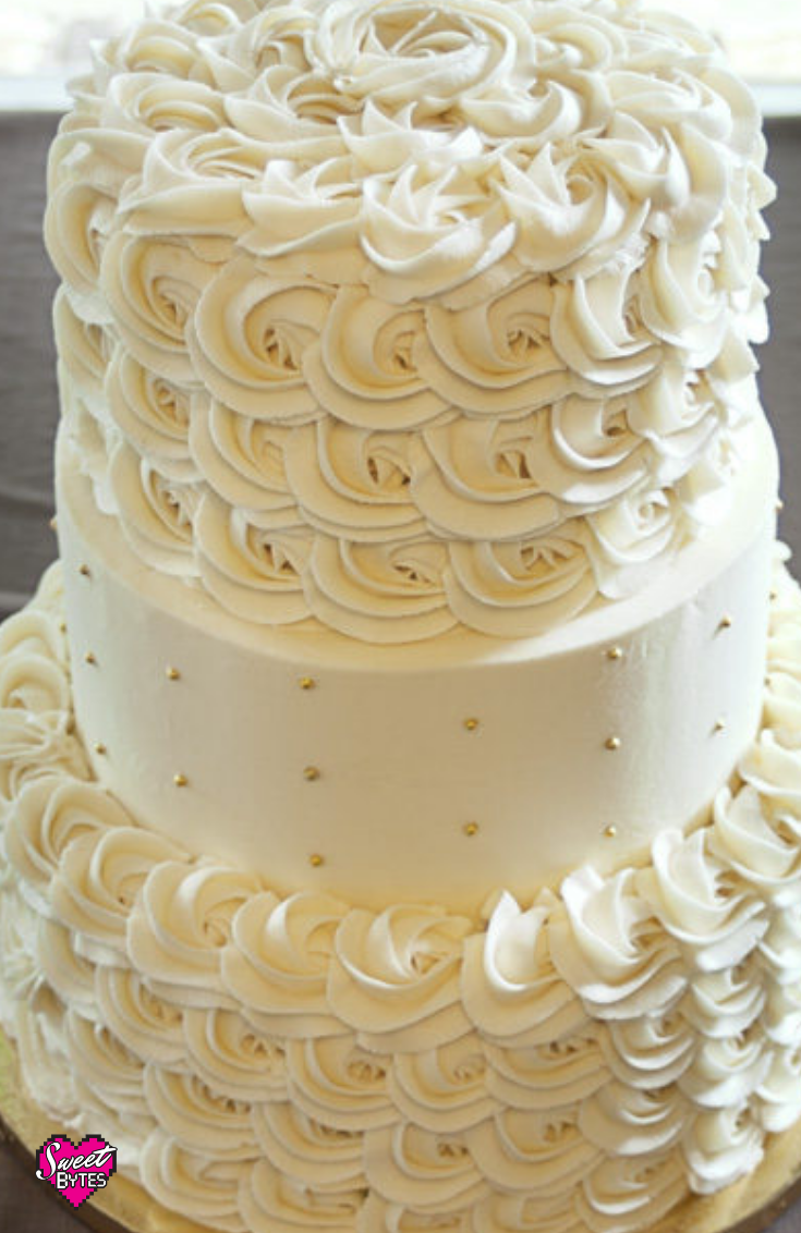 A close up of a 3 tiered cake with sweet bytes vanilla buttercream recipe