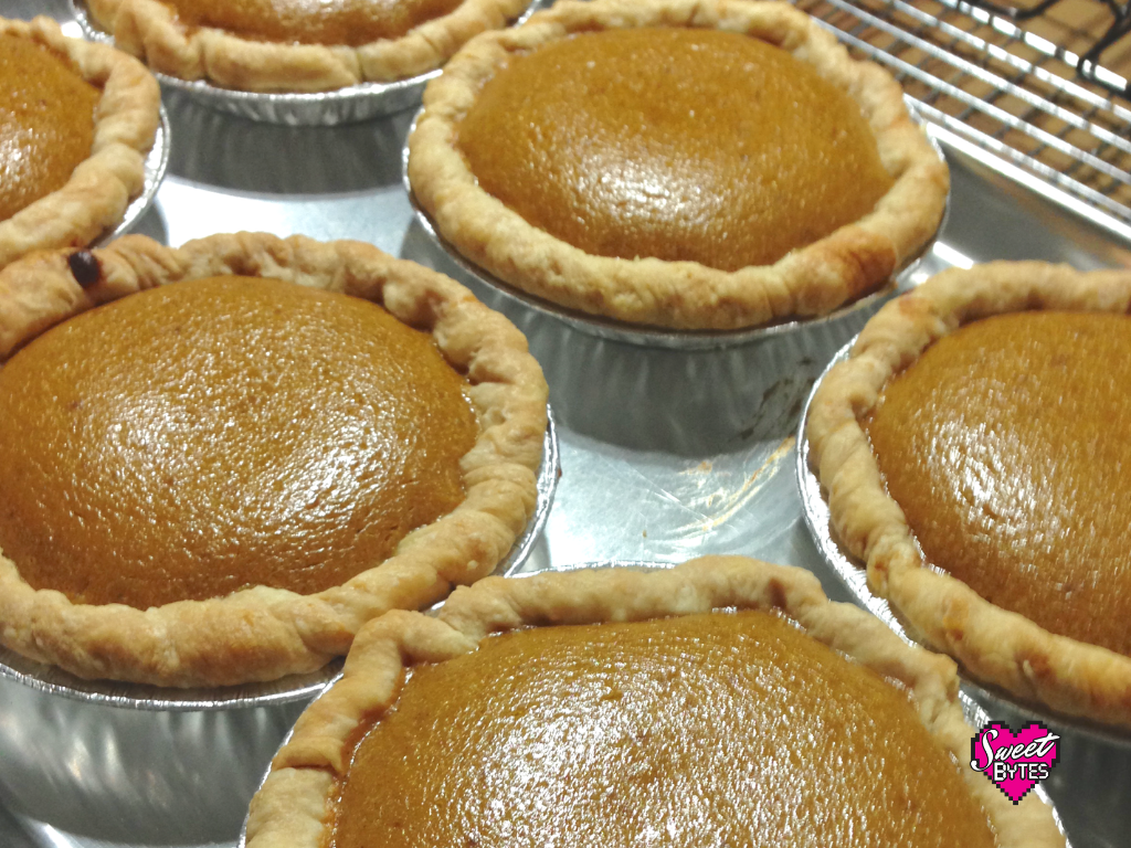Baking sheet with six small pumpkin pies fresh out of the oven