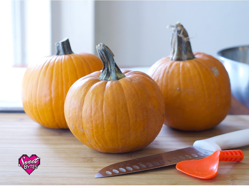 3 pie pumpkins sitting on a wooden table with a large knife and pumpkin scraping tool.