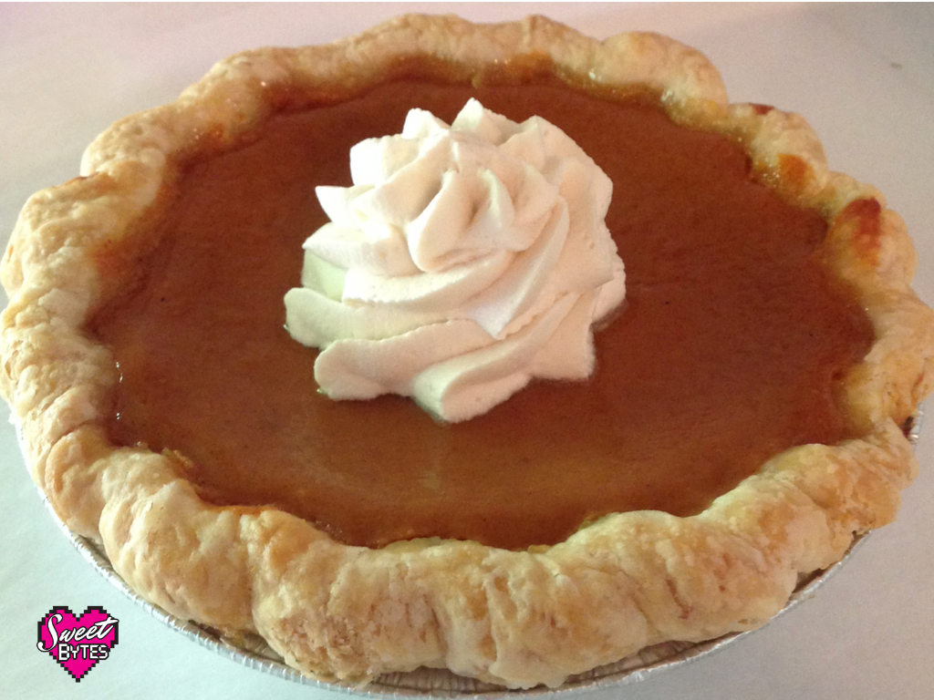 A baked pumpkin pie with a swirl of whipped cream in the center.
