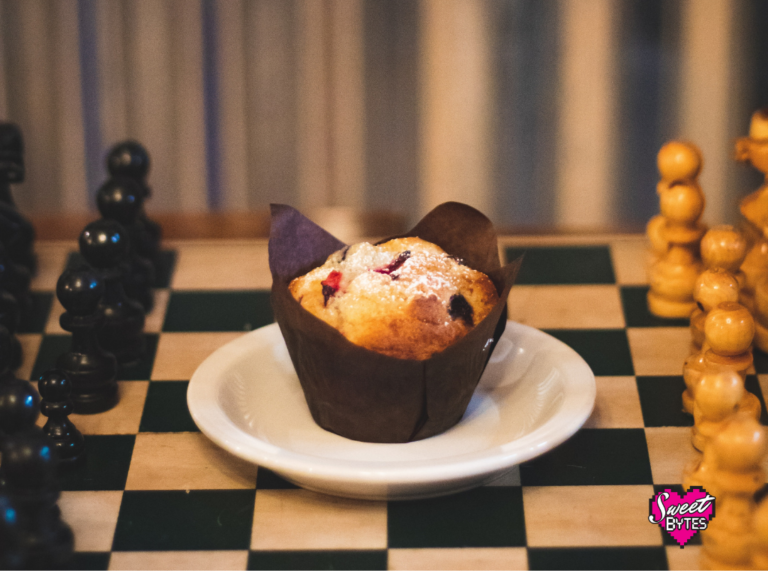 a muffin in a brown tulip style wrapper on a white saucer on the middle of a chess board