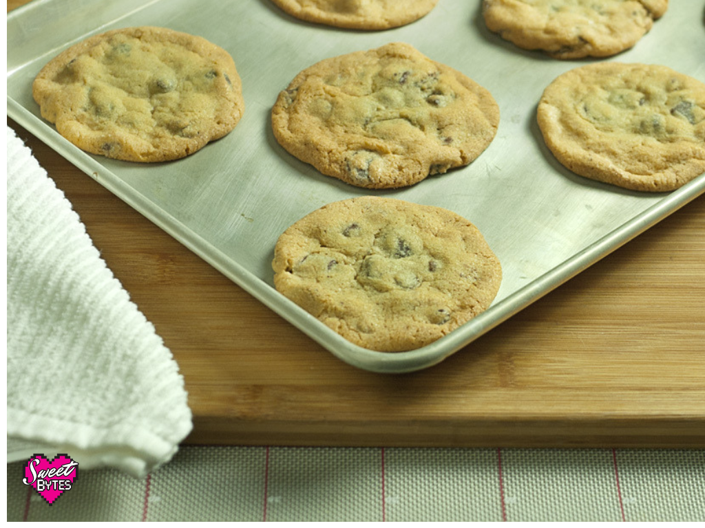 A baking sheet with large chocolate chip cookie baked on it