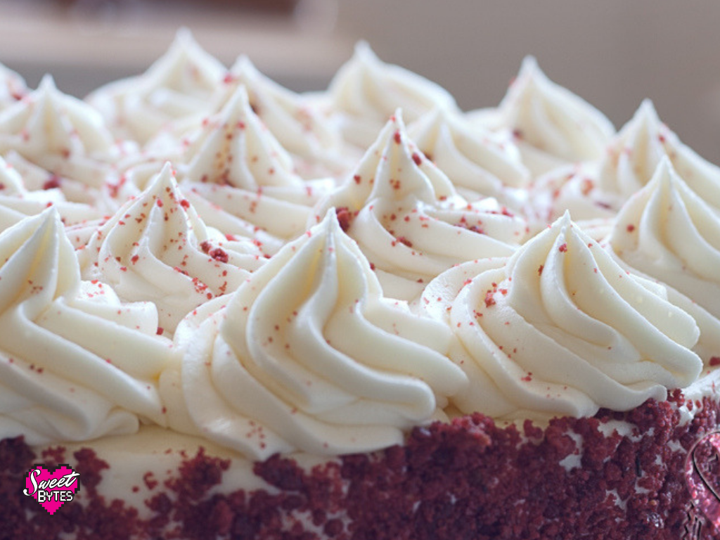 Peaks of cream cheese frosting on top of a red velvet cake