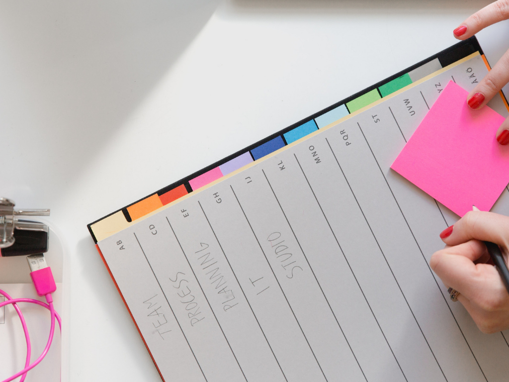 close up of a planner and a pink post it note