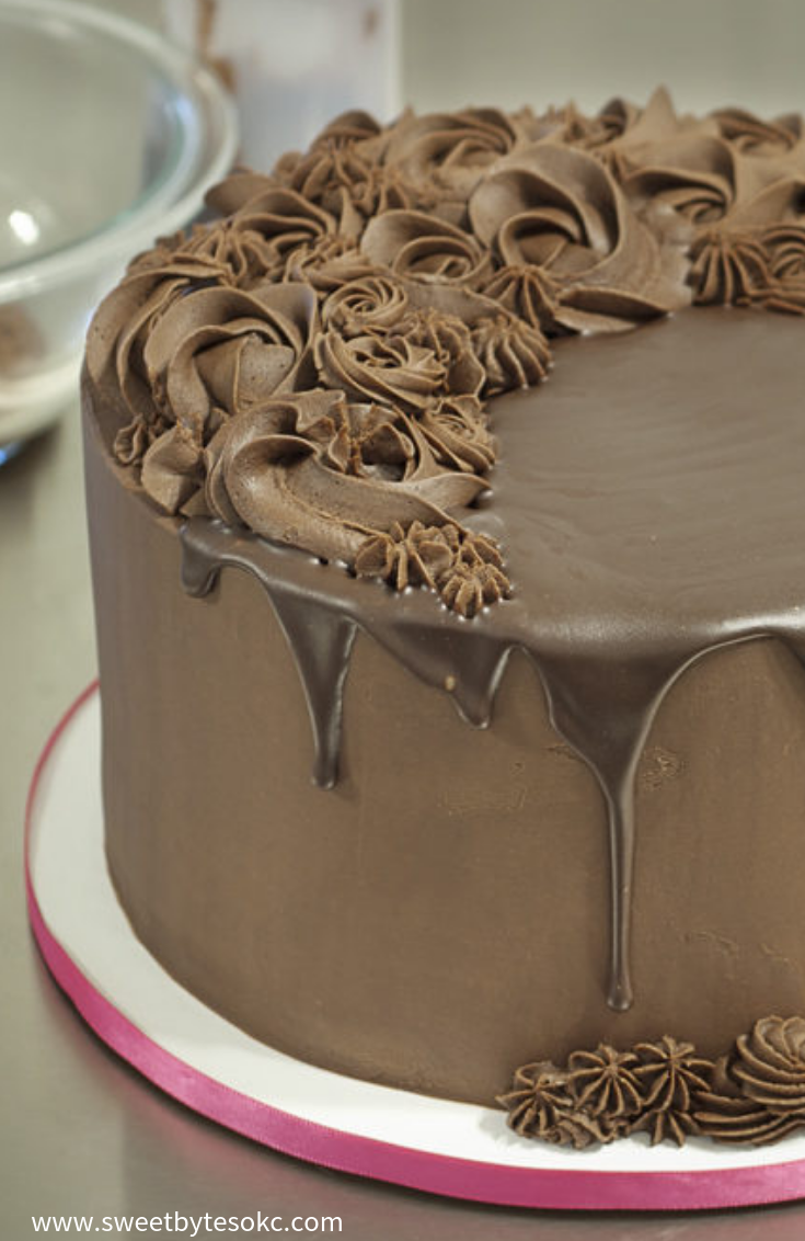 A cropped view of a ganache covered cake with piped decorations and a chocolate drip