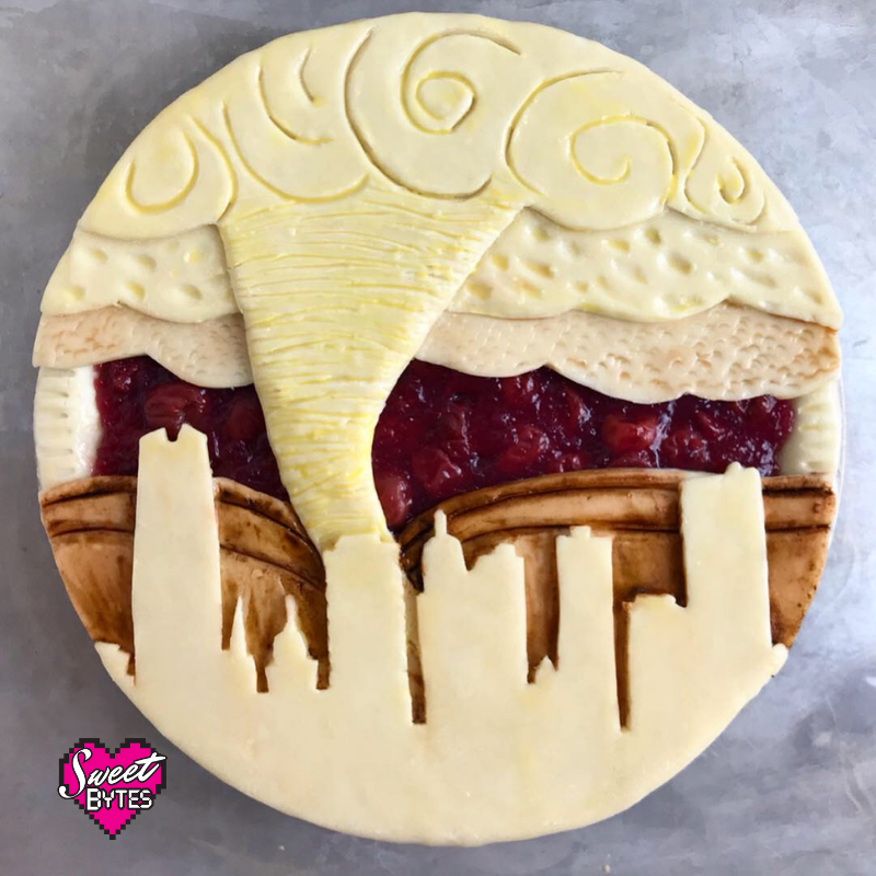Downtown Oklahoma City cut out of pie crust, painted with different colors of egg wash and a twister background
