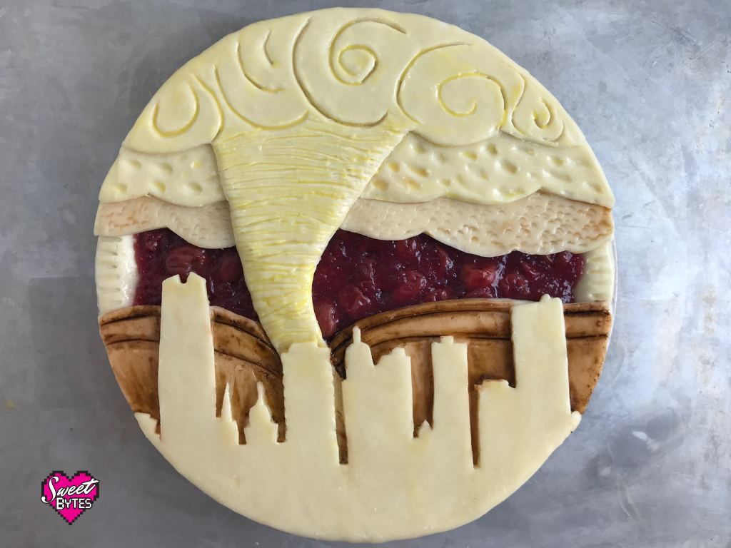 Cherry pie with a decorative pie crust showing downtown oklahoma city with a tornado in the background