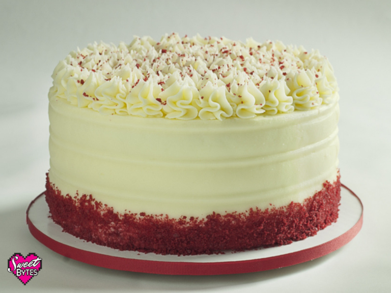 Red velvet cake with cream cheese frosting and red cake crumbs around the bottom