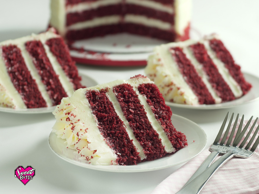 slices of red velvet cake with the whole red velvet layered cake in the background