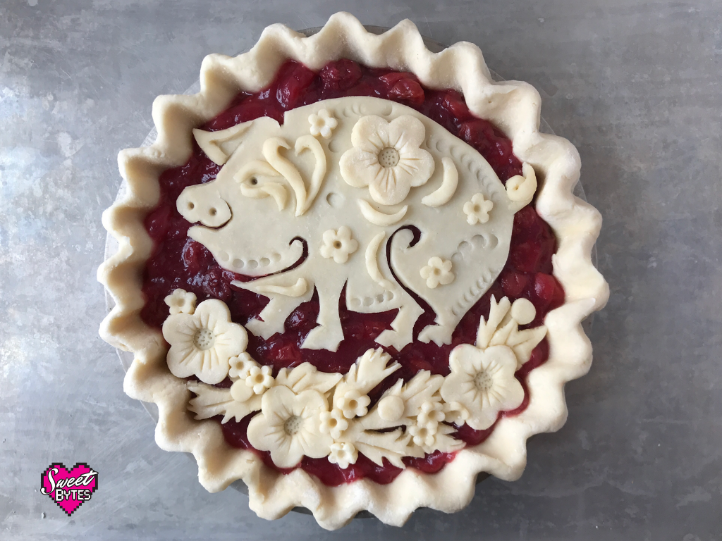 Unbaked cherry pie with flowers and a decorative pig celebrating Lunar New Year