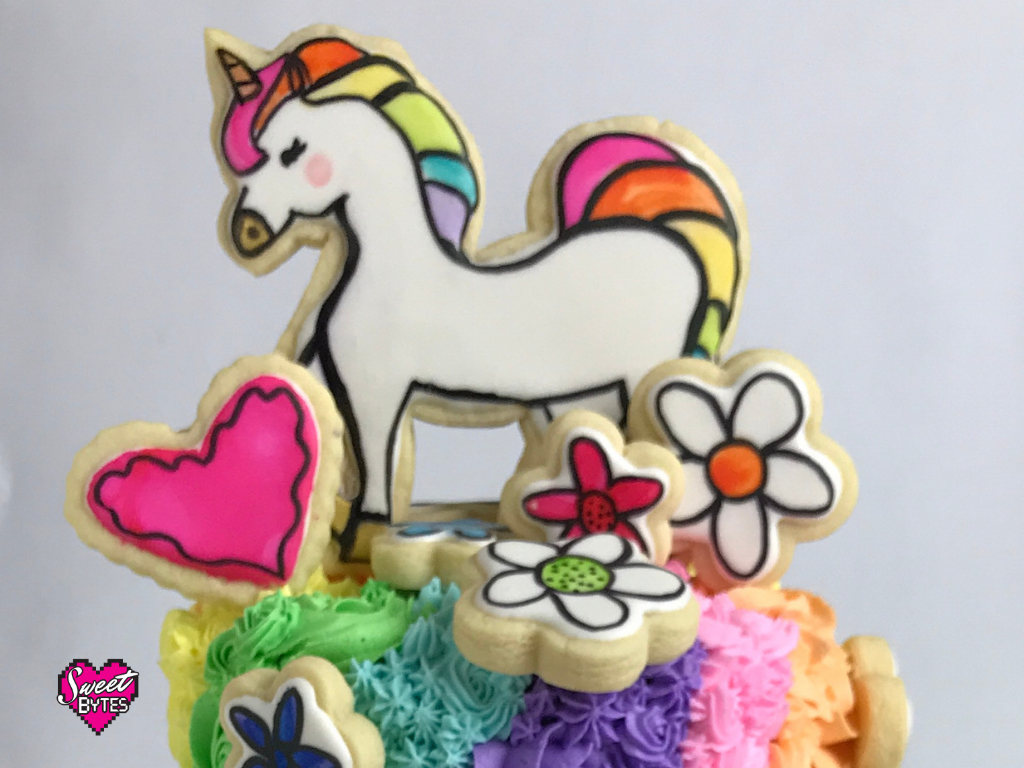 A handpainted unicorn sugar cookie, heart cookie, and flower cookie on top of a cake