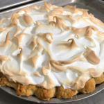 A beautiful lemon meringue pie with a toasted meringues sitting on a baking sheet